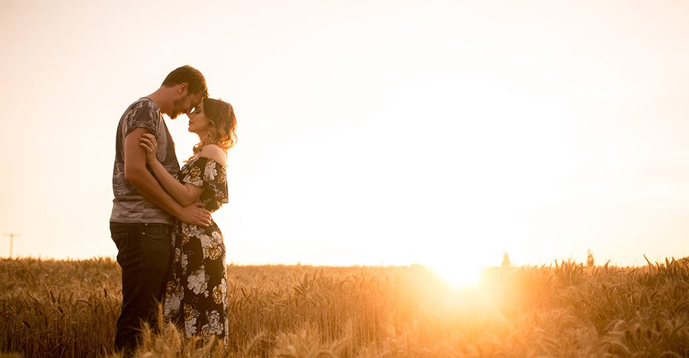 Engagement photo in wheat field at sunset