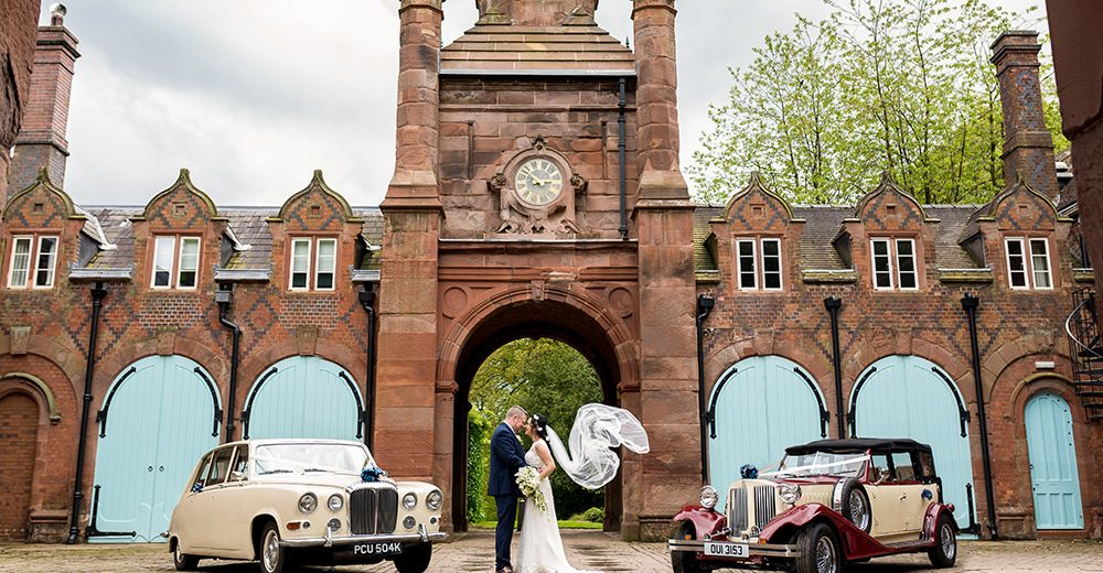 Bride and groom with wedding cars at Keele Hall Wedding Venue
